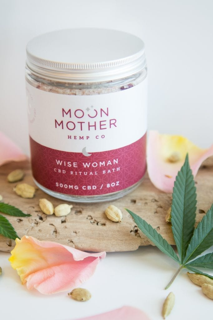 Wise Woman Ritual Bath surrounded by rose and hemp on wood